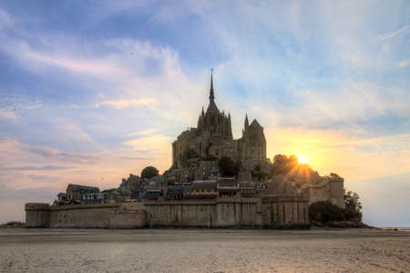 Beautiful view of historic landmark Le Mont Saint-Michel in Normandy, France, a famous  site and tourist attraction, at sunset Фото со стока