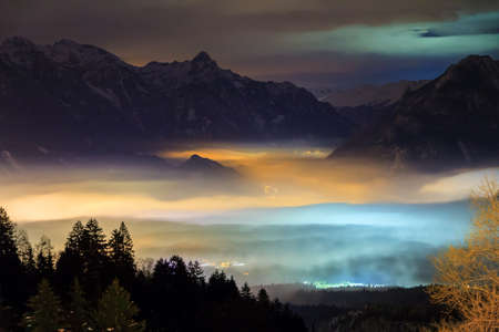 Beautiful winter night view of the city Brand in the valley of the Brandnertal in the mountains of the Alps in Vorarlberg, Austria, with illuminated fog clouds Stock Photo