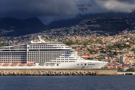Beautiful view of the harbor of Funchal, Madeira, seen from the Atlantic ocean with ominous clouds and a cruise ship Imagens