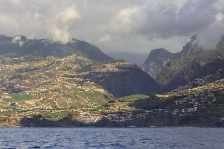Beautiful landscape view of the island of Madeira, seen from the Atlantic ocean, with ominous clouds over the mountains and gorges