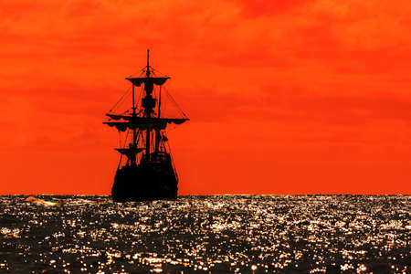 Beautiful silhouette view of a replica of the Santa Maria tallship of Columbus sailing the Atlantic ocean around Madeira island in summer at sunset Archivio Fotografico