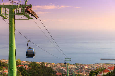 Beautiful cityscape view over the city of Funchal, Madeira, with the cable car going up Monte Funchal, at sunset Reklamní fotografie
