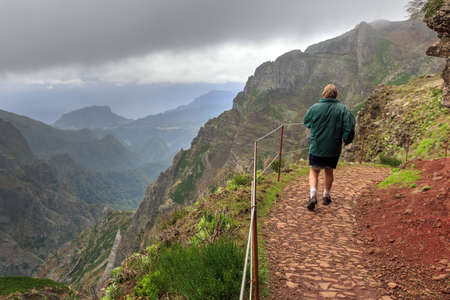 Senior tourist in the mountains of Madeira at Pico do Areeiro (Arieiro) while hiking to Pico Ruivo on a cloudy summer day with ominous sky and storm weather