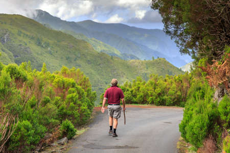 Beautiful landscape view of a hiking senior tourist on the 25 Fontes levada trail on the green island of Madeira