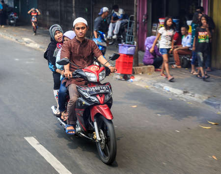 Typical view of people commuting with scooter in traffic in the streets of Jakarta, Indonesia, on August 2, 2015