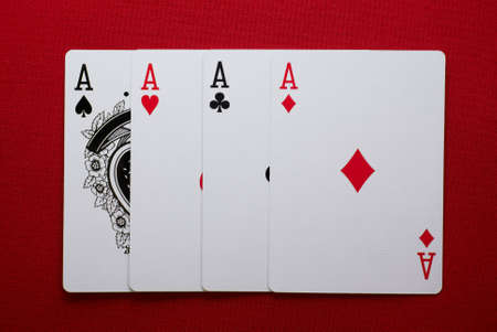 poker hand, for of one four aces on red felt Editorial