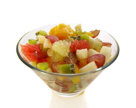 fruit salad in salad-bowl isolated over white, ingredients are kiwi, grapefruit grapes pear tangerine orange Stock Photo