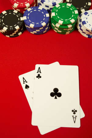 poker hand, pocket aces and button with colorful chips on red felt Stock Photo - 6196941