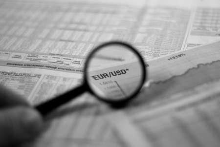 Lupa centrándose en un gráfico y la moneda dólar euro par en diario financiero  Foto de archivo - 6268108