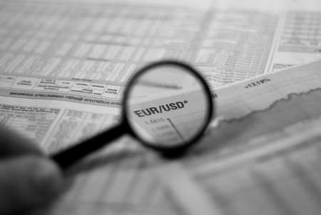 magnifying glass focusing on a graph and currency pair euro dollar in financial newspaper