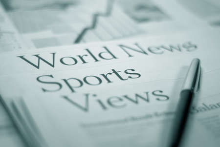 newspaper pages `world news` `sports` `views` with a pen