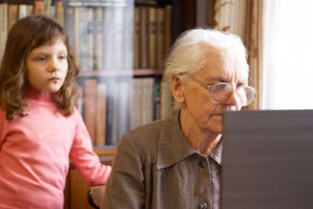 great-grandmother working with laptop and granddoughter  standing behind photo