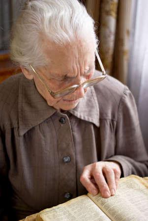 senior woman in glasses reading old Bible Stock Photo