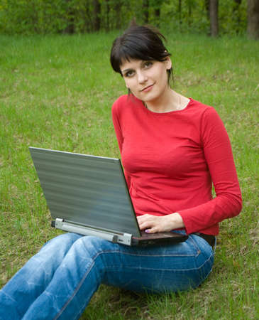 beautiful girl with a laptop on forest glade Stock Photo