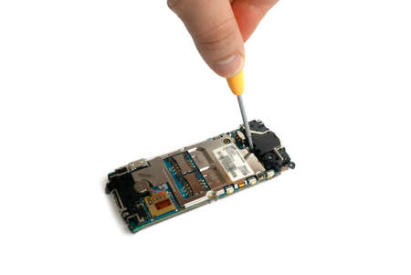 disassembled gsm cellphone with a screwdriver and hand of technician repairing the phone isolated over white
