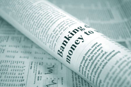 rolled-up newspaper on background of financial newspaper concept Foto de archivo