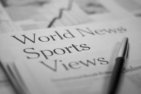 newspaper pages: world news, sports, views with a pen photo