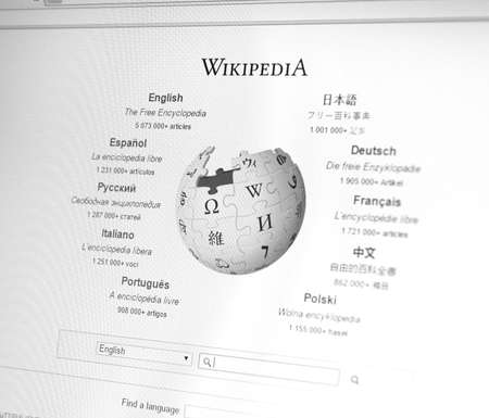 wiki: MONTREAL, CANADA - FEBRUARY, 2016: Wikipedia homepage on the computer screen under magnifying glass. Wikipedia is a free Internet encyclopedia.