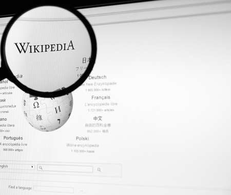 wiki wikipedia: MONTREAL, CANADA - FEBRUARY, 2016: Wikipedia homepage on the computer screen under magnifying glass. Wikipedia is a free Internet encyclopedia.