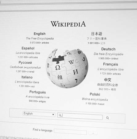wikipedia: MONTREAL, CANADA - FEBRUARY, 2016: Wikipedia homepage on the computer screen under magnifying glass. Wikipedia is a free Internet encyclopedia.