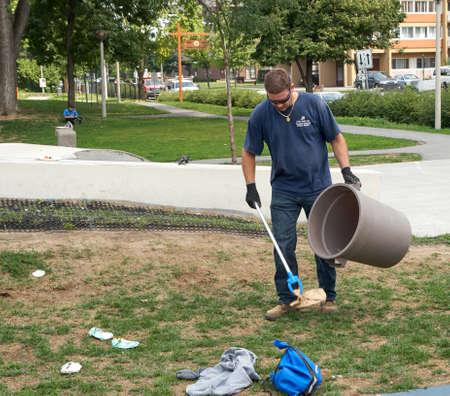 recolector de basura: Cote Saint-Luc, CANADÁ - agosto de 2015 - trabajador municipal recogida de basura en una calle.