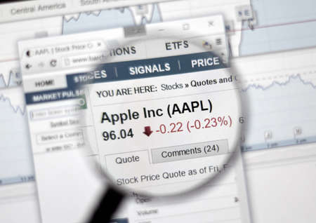 stock ticker: MONTREAL, CANADA - FEBRUARY, 2016 - AAPL - Apple Inc stock ticker with charts under magnifying glass.