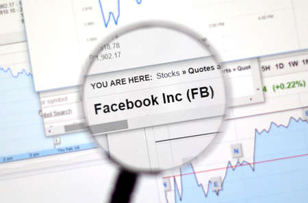 stock ticker: MONTREAL, CANADA - FEBRUARY, 2016 - FB - Facebook stock market ticker with charts under magnifying glass. Editorial