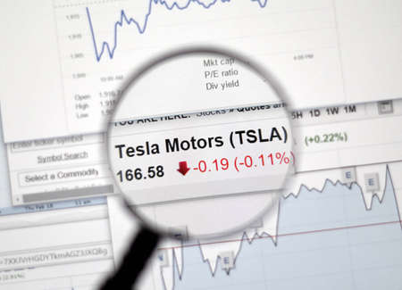 ticker: MONTREAL, CANADA - FEBRUARY, 2016 - TSLA - Tesla stock market ticker with charts under magnifying glass.
