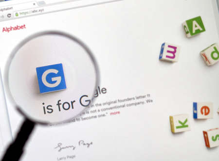 google chrome: MONTREAL, CANADA - FEBRUARY, 2016 - Alphabet Inc site under magnifying glass. Alphabet Inc. is a multinational conglomerate created in 2015 as the parent company of Google. Editorial