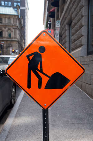 Ongoing road construction work, orange signs and traffic cones alerting motorists approaching the site. Focus on the sign.