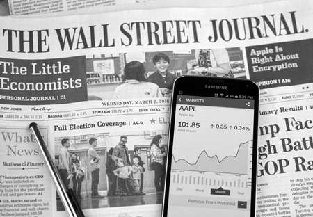 daily newspaper: MONTREAL, CANADA - MARCH 3, 2016 - The Wall Street Journal Newspaper with Samsung S5 on it. The Wall Street Journal Is an American international daily newspaper.