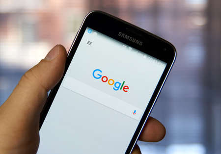 web page: MONTREAL, CANADA - MARCH 4, 2016 - Google mobile application on Samsung devices screen in a hand. Google is well known for its web search engine.