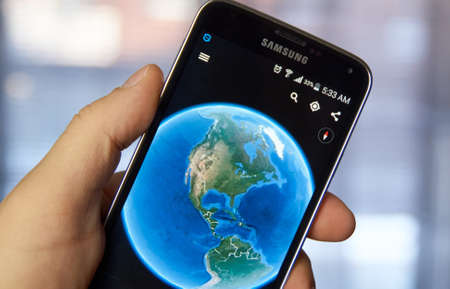 MONTREAL, CANADA - MARCH 4, 2016 - Google Earth application running on Samsung S5 in hand. The app allows anyone to travel around the world virtually. Editorial