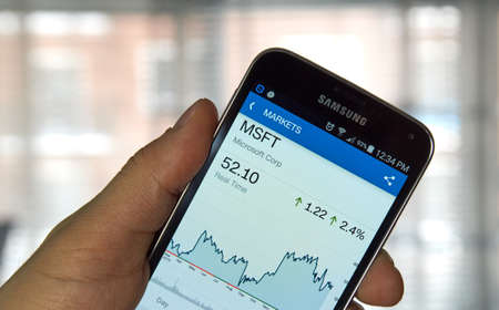 stock ticker: MONTREAL, CANADA - MARCH, 2016 -  MSFT - Microsoft stock ticker with chart on screen of mibile Samsung S5 in a hand. Microsoft Corporation is an American multinational technology company.