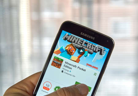samsung: MONTREAL, CANADA - MARCH, 2016 -  Minecraft mobile game on screen of Samsung S5 in a hand. Minecraft is a game where gamer digs mine and builds craft. Editorial