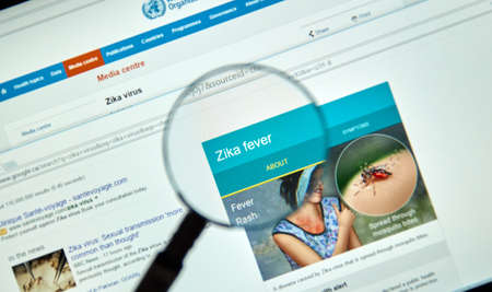 transmitted: MONTREAL, CANADA - MARCH  8, 2016 - Zika virus key facts on internet under magnifying glass. Zika virus is transmitted to people through the bite of an infected mosquito from the Aedes genus. Editorial