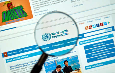 public health: MONTREAL, CANADA - MARCH 8, 2016 - World Health Organisation logo and web site under magnifying glass. The World Health Organization is a specialized agency of the United Nations that is concerned with international public health.