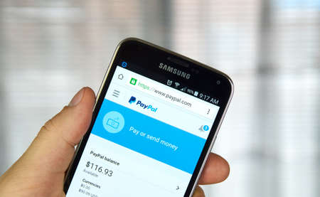 paypal: MONTREAL, CANADA - MARCH 8, 2016 - PayPal mobile application on screen of Samsung S5 in hand. Stock Photo