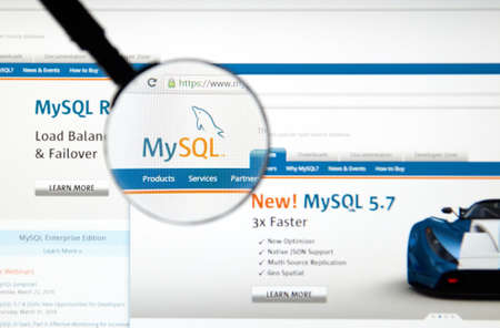 mysql: MONTREAL, CANADA - MARCH 5, 2016 - MySQL web page under magnifying glass. MySQL is a well known open-source relational database management system.
