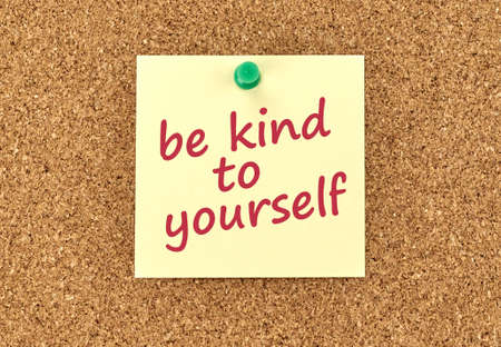 The phrase Be Kind To Yourself in red text on a yellow sticky note posted to a cork notice board. Stock Photo
