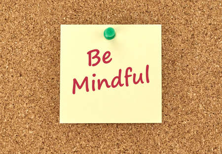 The phrase Be Mindful in red text on a yellow sticky note posted to a cork notice board.