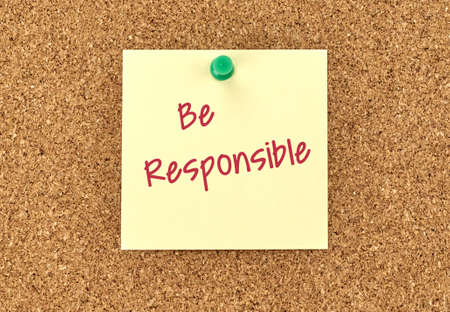 posted: The phrase Be Responsible in red text on a yellow sticky note posted to a cork notice board.
