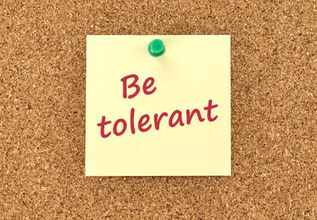 The phrase Be Tolerant in red text on a yellow sticky note posted to a cork notice board. Banque d'images