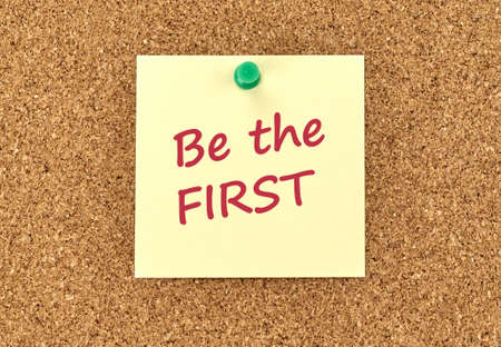 The phrase Be The First in red text on a yellow sticky note posted to a cork notice board. Stok Fotoğraf