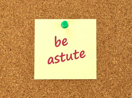 The phrase Be Astute in red text on a yellow sticky note posted to a cork notice board. Фото со стока