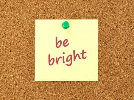 The phrase Be Bright in red text on a yellow sticky note posted to a cork notice board. Stock Photo