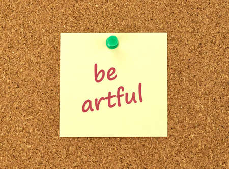positiveness: The phrase Be Artful in red text on a yellow sticky note posted to a cork notice board.