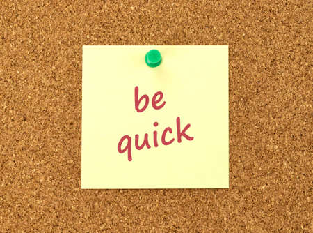 posted: The phrase Be Quick in red text on a yellow sticky note posted to a cork notice board. Stock Photo