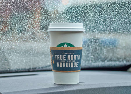 starbucks coffee: MONTREAL, CANADA - MARCH 16, 2016 - Starbucks coffee cup in a car on a raining day. Starbucks is one of the popular American coffee company and coffeehouse chain. Editorial