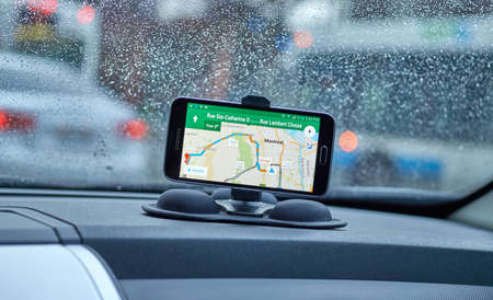MONTREAL, CANADA - MARCH 15, 2016 - GPS application Google Maps on Samsung S5 im a car over wet windows background. Google Maps is one of the most popular GPS applications.